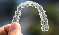 A person holding an Invisalign aligner