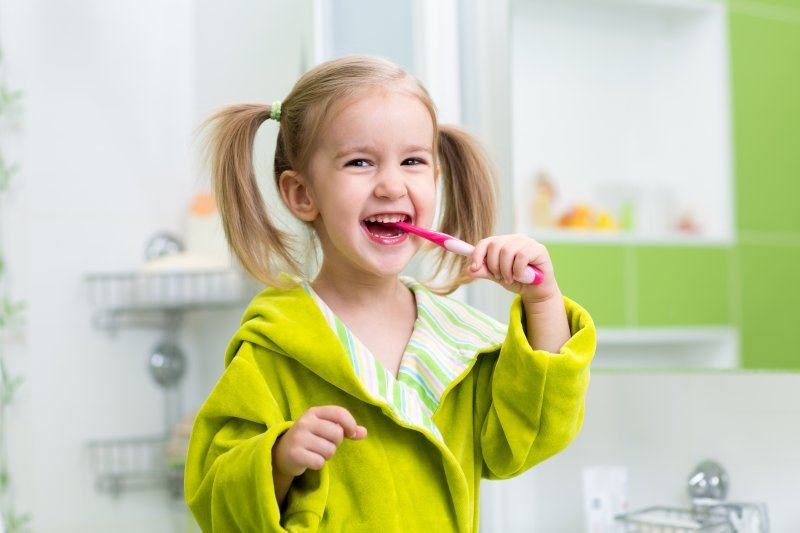 little girl smiling brushing her teeth