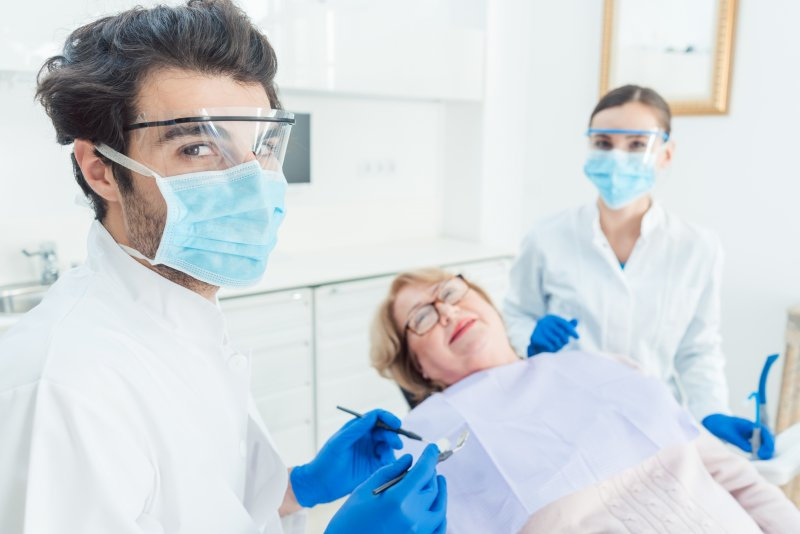 Dentist in Greenfield wearing PPE with patient