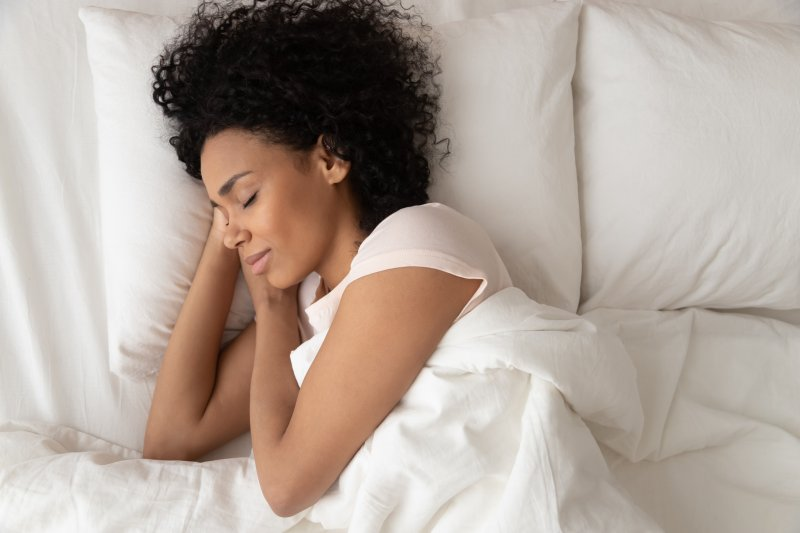 Woman sleeping in bed with hands under head